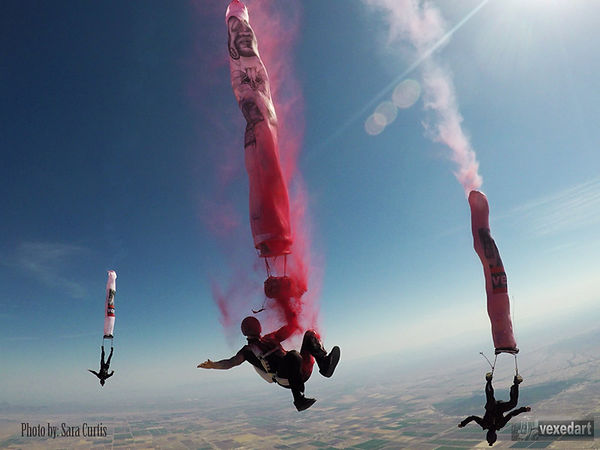 Artist paints the sky with paint after jumping out of a plane