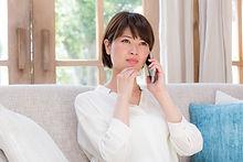 ソファーに座り電話をする女性画像