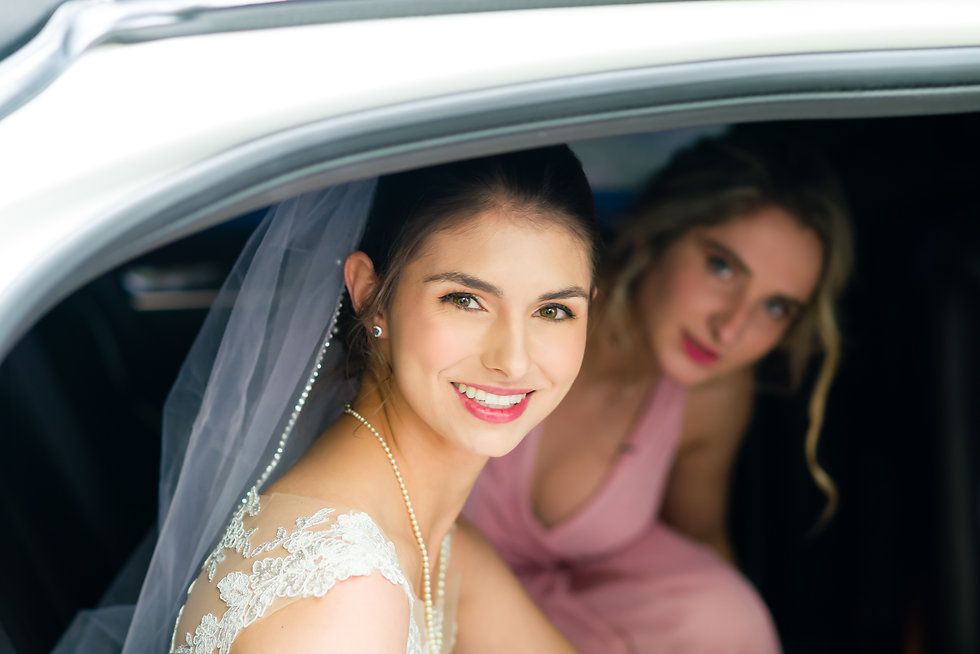 Bride in a limo smiling for the camera on her wedding day, heading to the wedding venue in Calgary - Photo taken by Pierre-Luc Cormier Photography