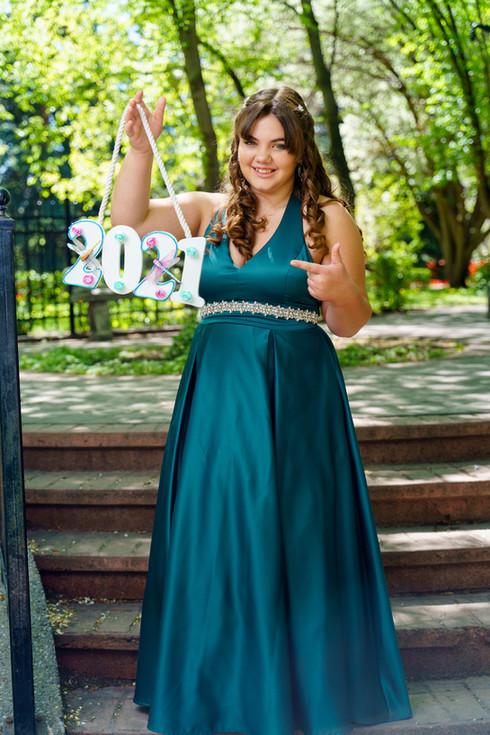 Kristin in her grad dress in a flower garden celebrating her 2021 Grad