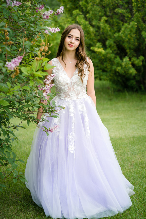 New Grad in her purple & white graduation dress for her grad photo session with lilacs in Calgary
