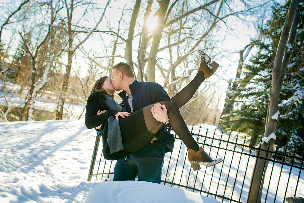 Winter Engagement Kiss - future bride and groom kissing in Gerry Shaw Garden in Calgary