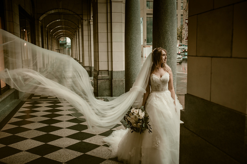 Bridal Photos on Stephen Avenue Calgary - Bride with Long Veil flowing through the wind on a rainy day