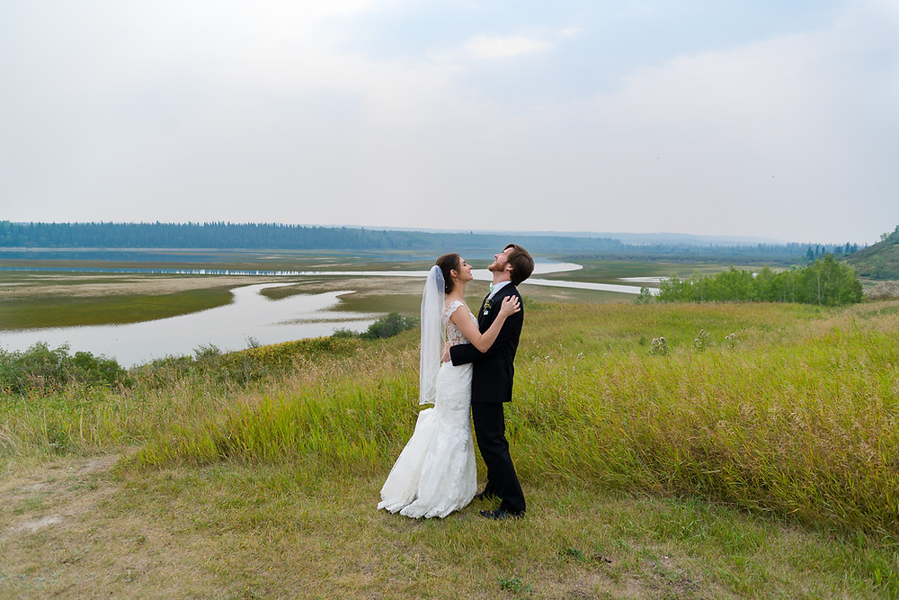 Bride and Groom Sharing Laughs During their wedding Photos in Glenmore Park, Calgary