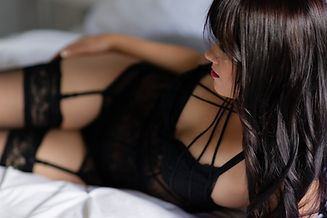 Woman client wearing black lingerie for a Christmas Boudoir sesison in Calgary