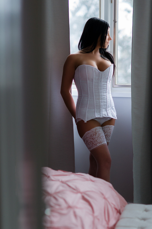 Woman in white corset and garters for boudoir portrait in Calgary