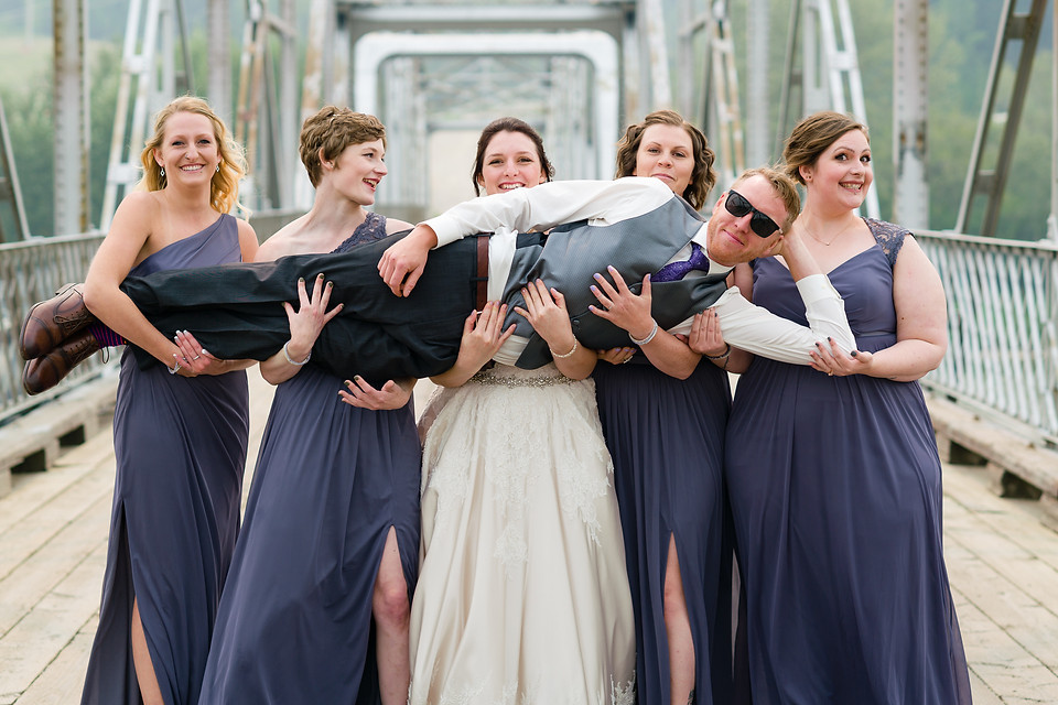 Randi and Luc Wedding in Cochrane Alberta - Bridesmaids Carrying the Groom