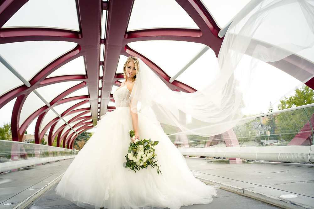 Bride at the Peace Bridge in Calgary - Dreamy bridal veil flowing in the winds while the bride holds wedding flowers