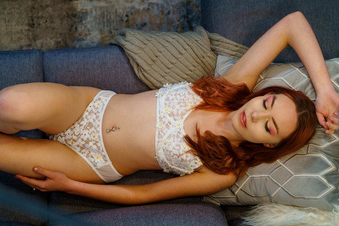 Woman with red hair in two piece white lace bra and panties lingerie top down view on couch for lifestyle boudoir