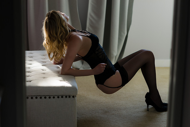 Woman in black lingerie piece, heels and garters