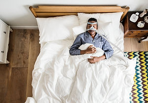 Man sleeping with an anti-snoring mask.j