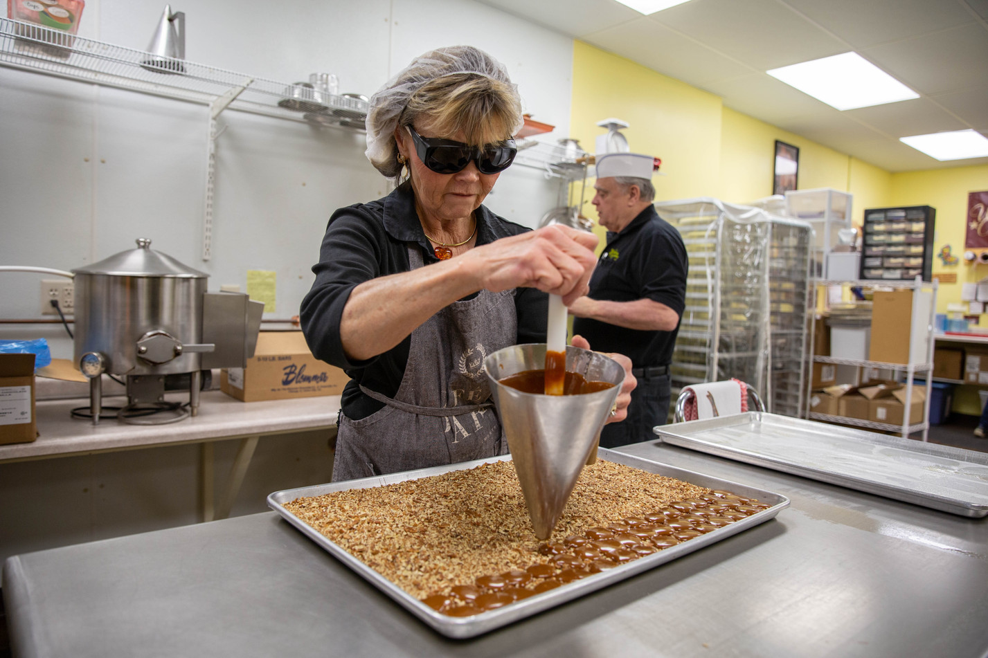 """Watertown Confectionery's Vickie Marotz funnels globs of freshly-made caramel onto a tray of crushed pecans while making a batch of turtles on Wednesday, Jan. 23, while her husband Mike prepares more caramel. The confectionery sells dozens of different chocolate candies, including dark chocolate caramels with sea salt, milk or dark chocolate Mint Meltaways, chocolate-covered peanut butter cups, milk and dark chocolate turtles and much more. """"We have such an array of chocolates,"""" Marotz said. """"I'm never bored because there's always something to do."""" ©2019 Grace Ramey"""