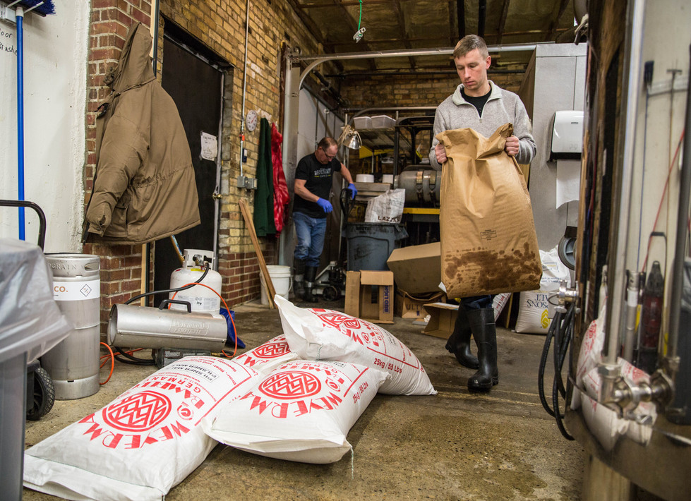 Don Walraven, left, and Josh Crance, right, set out bags of Pilsner Malt, golden naked oats and hulled barley flakes for an Irish Blonde beer the two will brew for St. Patrick's Day on Friday, Feb. 9 in the Watertown Brewing Co.'s brewery. Walraven, who has only been brewing beer himself since about six months ago, said he approached owning a brewery backwards, first buying a restaurant and hop yard and then learning to brew himself. ©2018 Grace Ramey