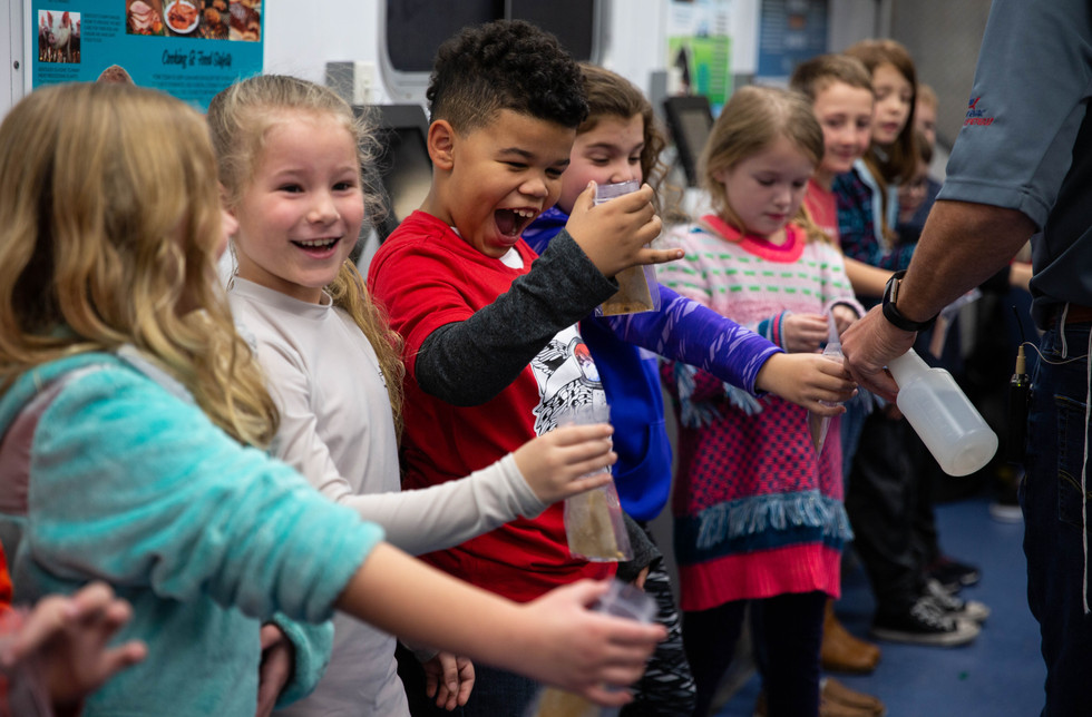 North Warren Elementary School second grader Malik Levy reacts to Kentucky Department of Agriculture Mobile Science Activity Center Program Coordinator Jason Hodge spraying water in the bag in which he planted a soybean during a germination activity on Monday, Dec. 16, 2019. The students planted a soybean seed in a bag containing a paper towel representing soil, a paper cutout sun, confetti representing fertilizer and some water. ©2019 Grace Ramey