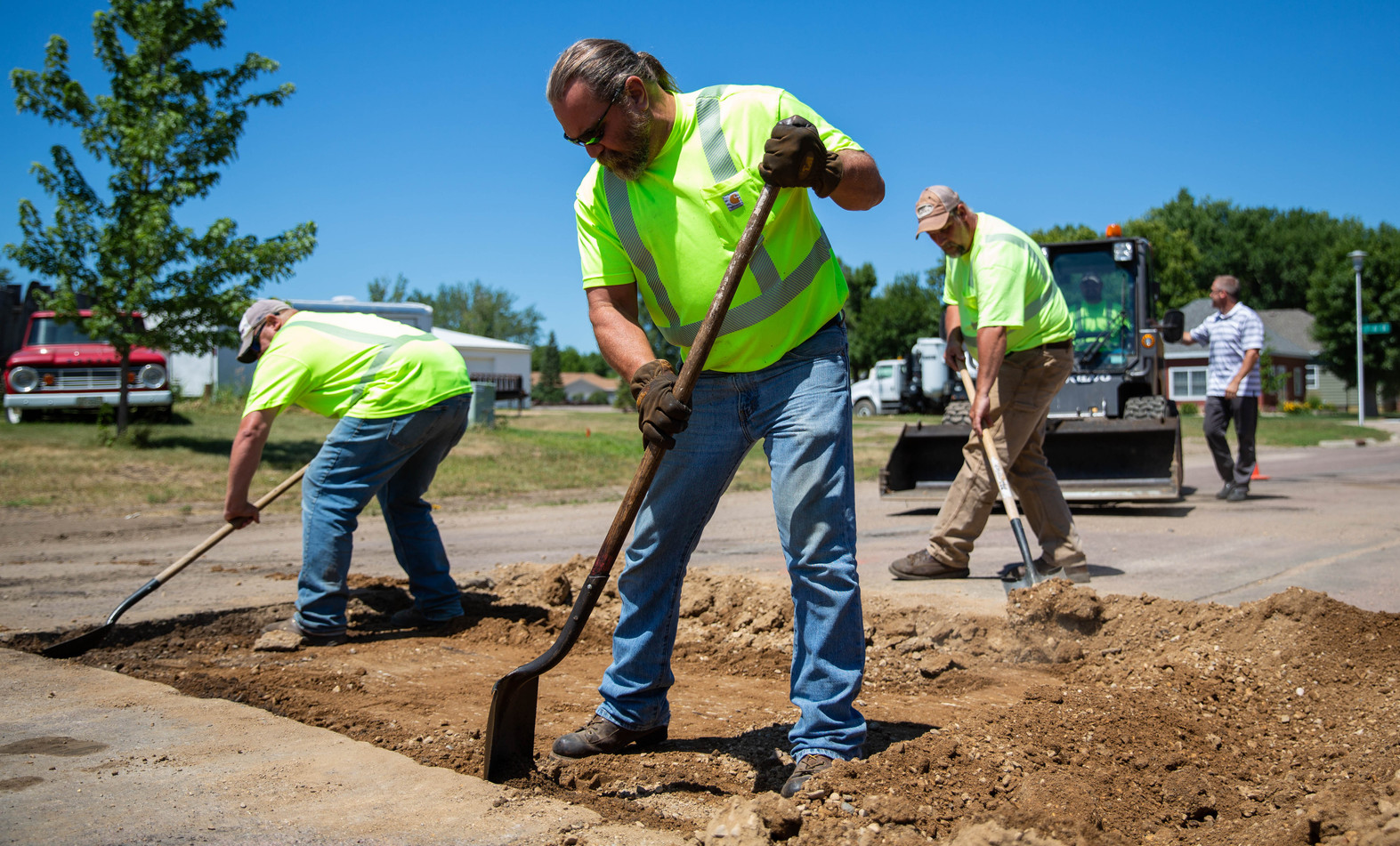 From left, Watertown Street Department employees Scott Brinkman, Keith Johnson and Jan Dailey help dig out old gravel from a trench they patched July 16, 2018, on 4th St. SW and 4th Avenue SW. When doing patchwork, the road crew starts by cutting and digging out the old asphalt, gravel and dirt, then put in two lifts of 1 1/2 to 2 inches of hot asphalt heated at approximately 280 degrees, lute and roll the new asphalt smooth and finish by letting it sit to cool for several hours. ©2018 Grace Ramey