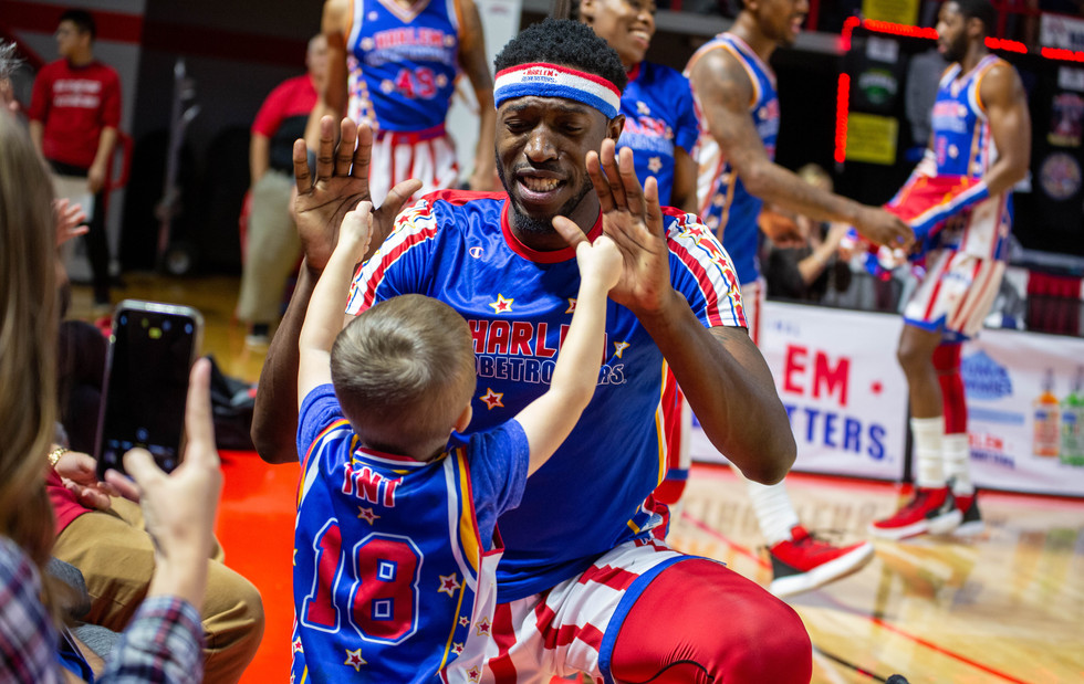 """Harlem Globetrotter Bounce Crutchfield gives Rex Crane, 4, of Bowling Green a high five during the team's """"Pushing The Limits"""" World Tour stop at E. A. Diddle Arena on Tuesday, Jan. 14, 2020. ©2020 Grace Ramey"""
