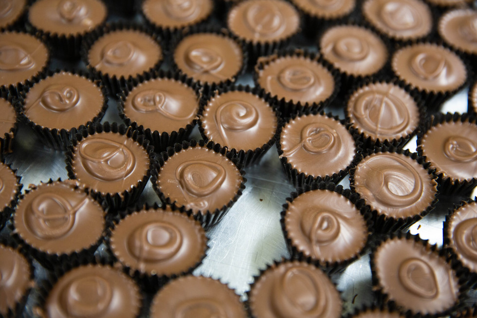 A batch of peanut butter cups sit cooling on a tray in the kitchen of the Watertown Confectionery on Wednesday, Jan. 23. The Marotzes use different designs on the top of their chocolates to indicate the type of candy they are. ©2019 Grace Ramey