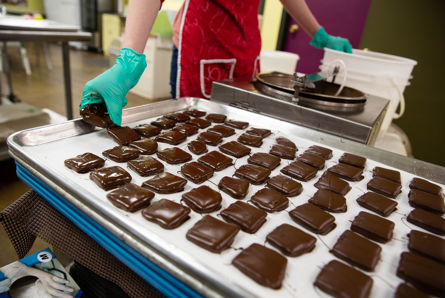 """Watertown Confectionery employee Hal Holdahl makes a tray of chocolate-covered toffee squares she dipped one by one into a bowl of dark chocolate on Wednesday, Jan. 23. Every piece of chocolate the confectionery sells is handmade and handdipped, so no two chocolates are the same. """"It's a lot of work, but it's also a lot of fun,"""" Holdahl said. ©2019 Grace Ramey"""