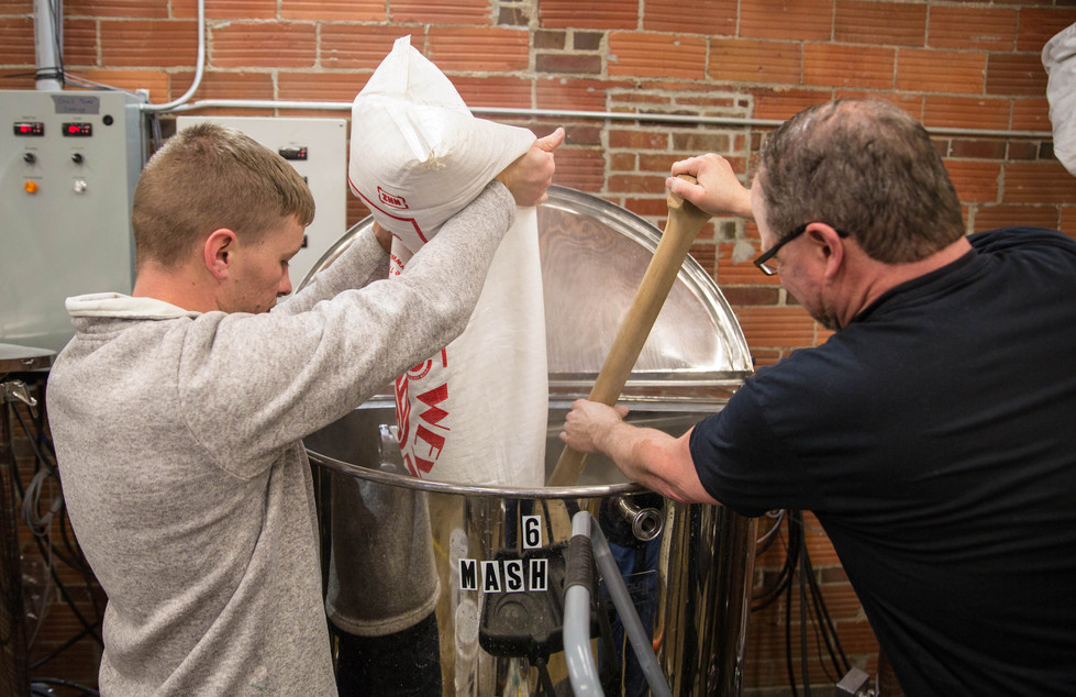Josh Crance, left, and  Don Walraven, right, pour bags of Pilsner Malt, golden naked oats and hulled barley flakes into the mash tank for an Irish Blonde beer for St. Patrick's Day on Friday, Feb. 9 in the Watertown Brewing Co.'s brewery. The mixture will sit in the mash tank for around 30 minutes, rinsing the sugars out of the grain before transferring to the kettle to brew with the hops. ©2018 Grace Ramey