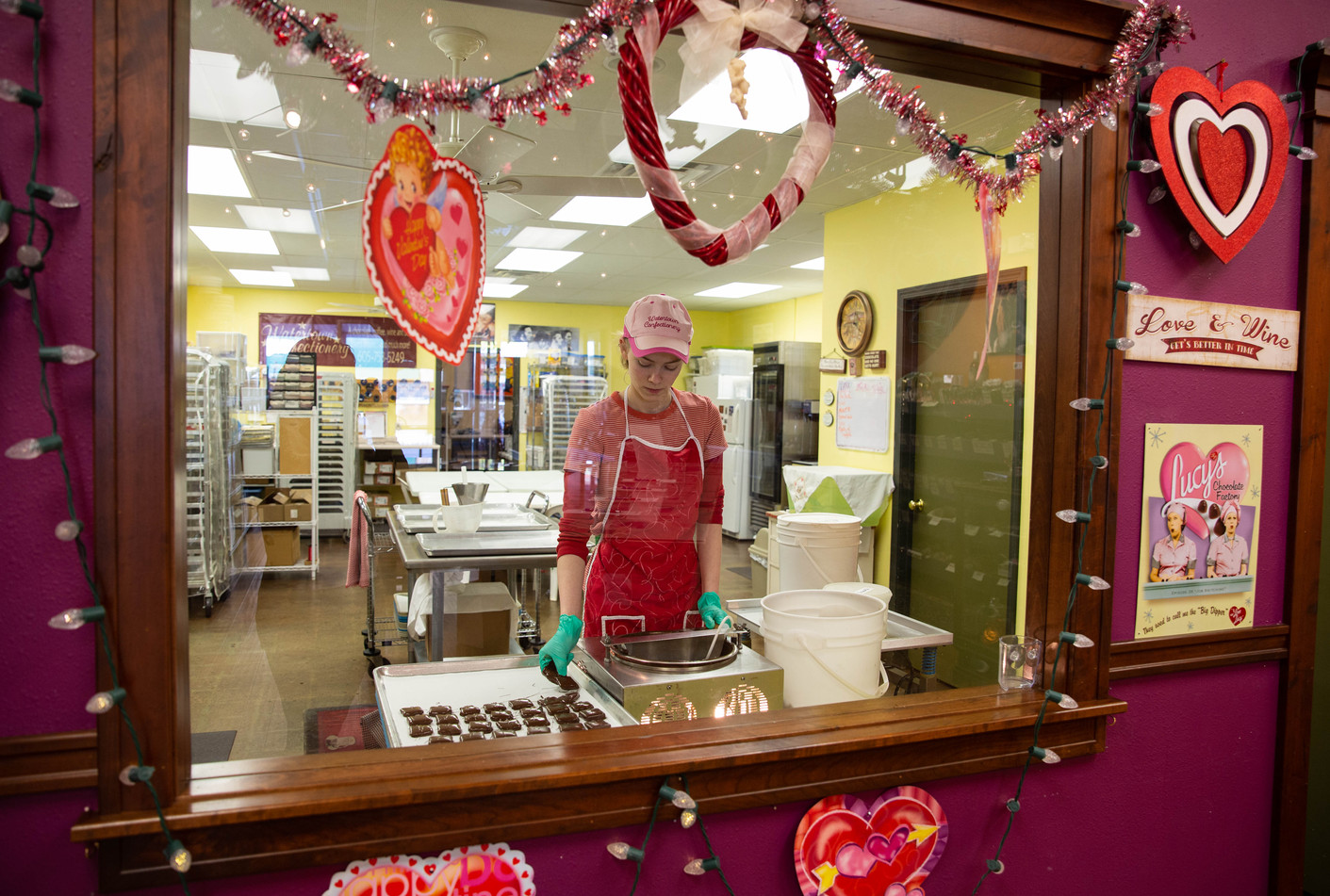 """Watertown Confectionery employee Hal Holdahl dips toffee squares one by one in a bowl of dark chocolate on Wednesday, Jan. 23. Every piece of chocolate the confectionery sells is handmade and handdipped, so no two chocolates are the same. """"It's a lot of work, but it's also a lot of fun,"""" Holdahl said. ©2019 Grace Ramey"""