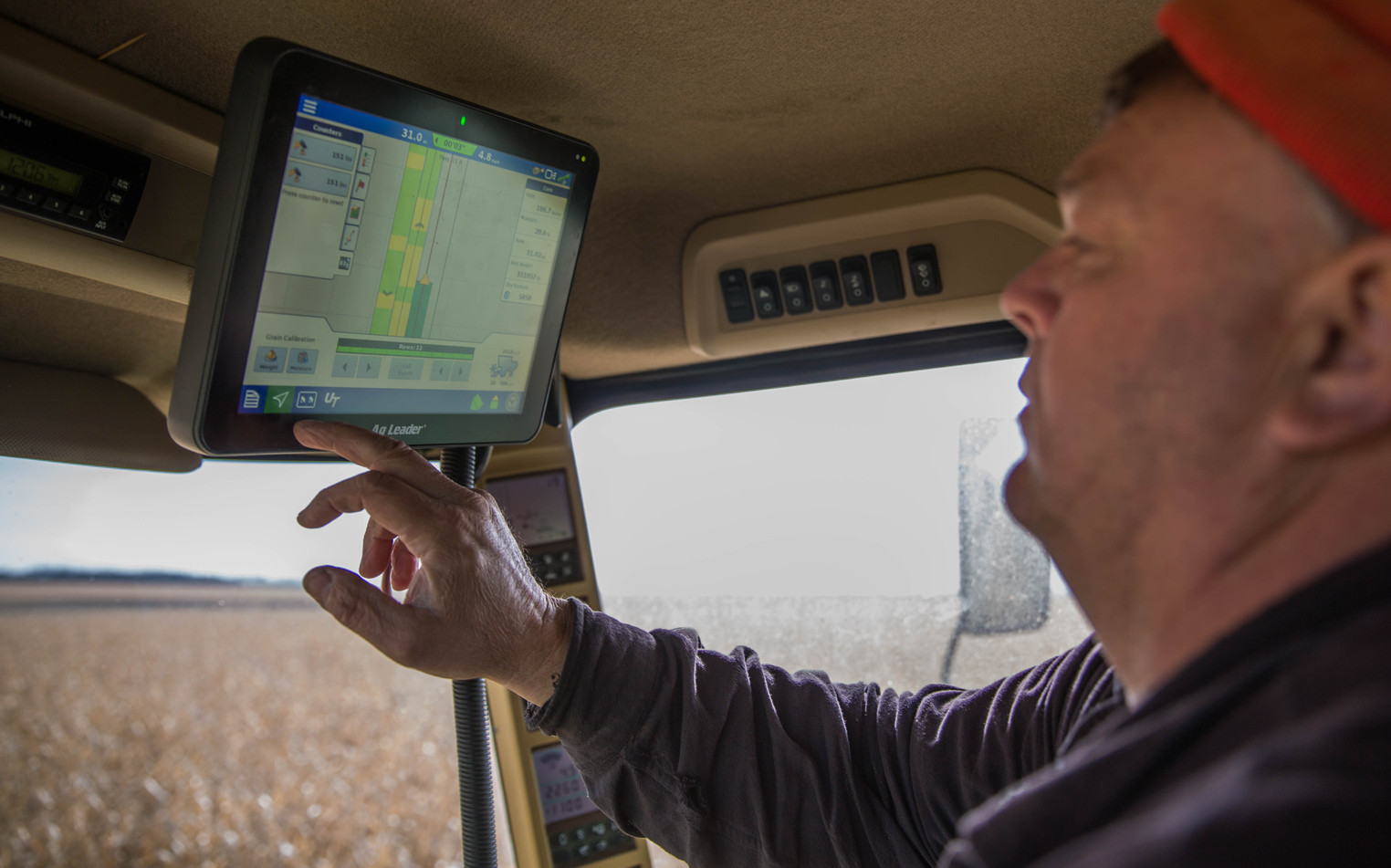 Jim Thyen checks the GPS and readings in the combine during dry corn harvest on Tuesday, Oct. 31 in Waverly. The combine can self-drive, measure the number of bushels being collected per acre, show parts of the fields that are more or less productive and more. Farming technology continually improves, making harvest more time-efficient. ©2017 Grace Ramey