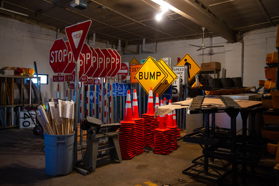 Portable traffic signs, used when traffic signals go down or in construction zones, sit stored in one of the buildings in the Watertown Street Department complex. Permanent signs, which are assembled when needed, are bolted to stubs in the ground, making them easier to replace if they get damaged. ©2018 Grace Ramey