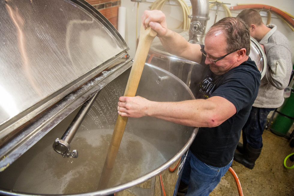 """Don Walraven stirs the grain at the bottom of the mash tank with a wooden paddle he calls """"Thor's Spoon,"""" while boiling water from the hot liquor tank sprinkles in and filters through the tank on Friday, Feb. 9 in the Watertown Brewing Co.'s brewery. The sprinkling is Walraven's favorite part of the process. """"I like the smell, the looks and the action,"""" he said, """"because you can actually see the sugars getting filtered out."""" ©2018 Grace Ramey"""