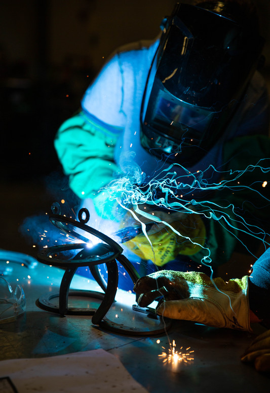 Community members practice welding skills