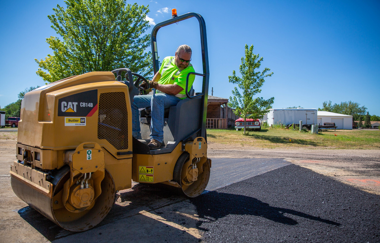 Keith Johnson of the Watertown Street Department drives a roller over a trench the Department patched on 4th St. SW at an angle to reduce a drop off once the asphalt cools and hardens. The roller uses vibrations to compact the asphalt down and its weight to smooth it out. ©2018 Grace Ramey
