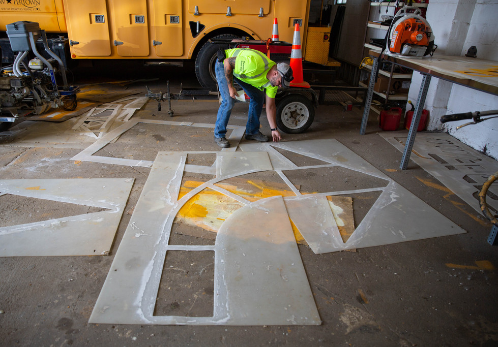 Rick Jacobson, the Watertown Street Department sign and signal maintenance lead, sets out a stencil used to paint turn markings on July 16, 2018, in the Street Department complex. All street markings, except parking stalls and curbs, are created by using rubber-based traffic paint mixed with small glass beads that make the marking reflective. ©2018 Grace Ramey