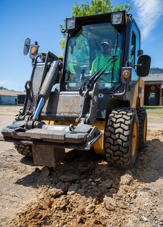 Mark Wilson of the Watertown Street Department uses a skidsteer to unpack gravel from a trench he and three other Street Department employees patched July 16, 2018, on 4th St. SW and 4th Avenue SW. A contractor had put in new water and sewer services for a home and filled it with packed gravel until the Street Department could repave the patch. ©2018 Grace Ramey