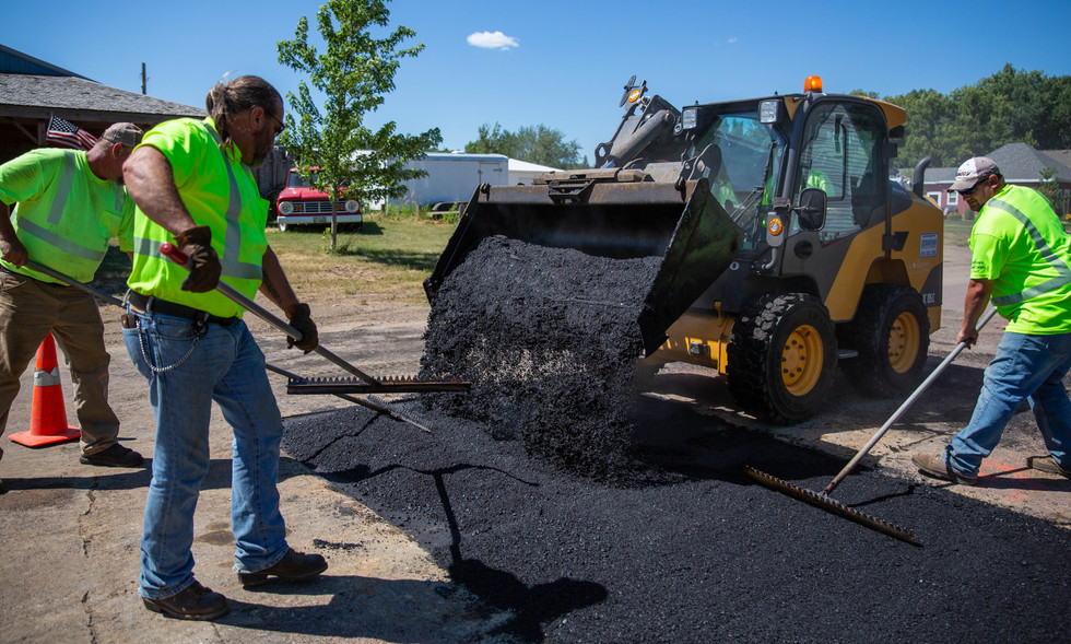 Project lead Mark Wilson dumps hot asphalt onto a trench the Street Department patched on 4th St. SW on July 16, 2018, while Jan Dailey, Keith Johnson and Scott Brinkman smooth the asphalt with lutes. After the hot asphalt is smoothed with the lutes, a roller is driven over the patch to pack it down with weight and vibrations. ©2018 Grace Ramey
