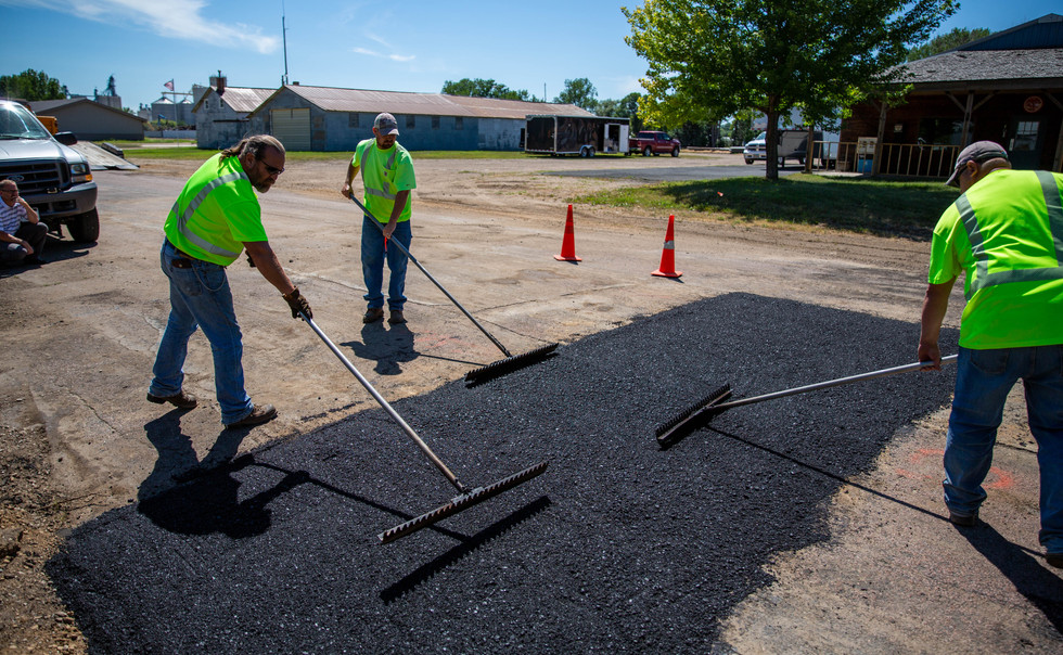 From left, Watertown Street Department employees Keith Johnson, Mark Wilson and Scott Brinkman use lutes to smooth hot asphalt over a trench the Department patched on 4th St. SW on July 16, 2018. Once the hot asphalt is smoothed with the lutes, a roller is driven over the patch to pack it down with weight and vibrations. ©2018 Grace Ramey