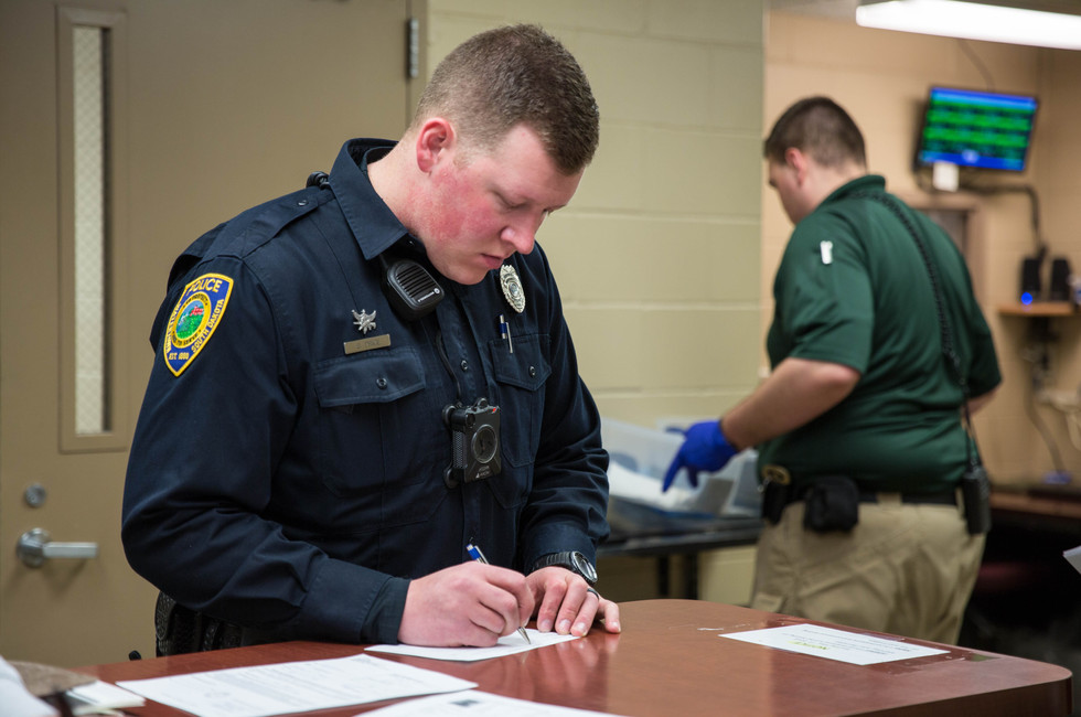 WPD Corporal Scott Price fills out a custody authorization form after bringing a suspect with a warrant out for his arrest into the sheriff's department on May 11, 2018. The man, who had failed to report for a DUI-related program, was taken to the sheriff's department to be processed and held for the weekend. ©2018 Grace Ramey