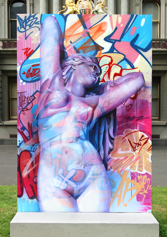 Colourful image of a classical sculpture with graffiti.