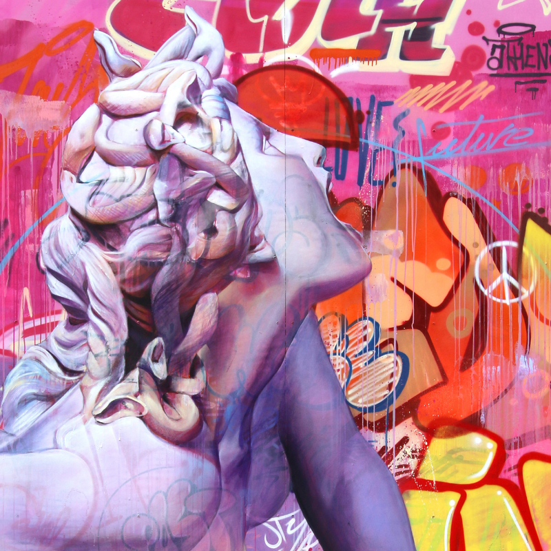 Bright artwork depicting a sculpture of Medusa and bright pink graffiti.