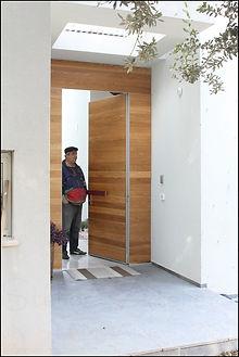 דלת כניסה ראשית בחיפוי עץ גושני בנוף ים