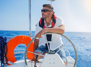 Young man sailing yacht steering wheel v