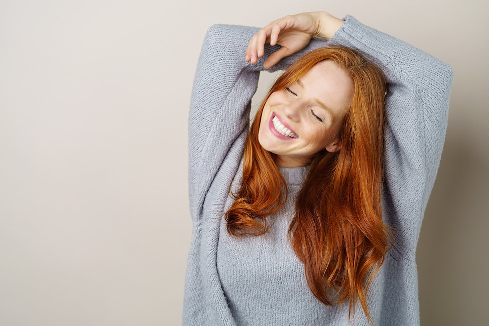 Happy carefree young redhead woman with a cute grin posing with her hands over her head an