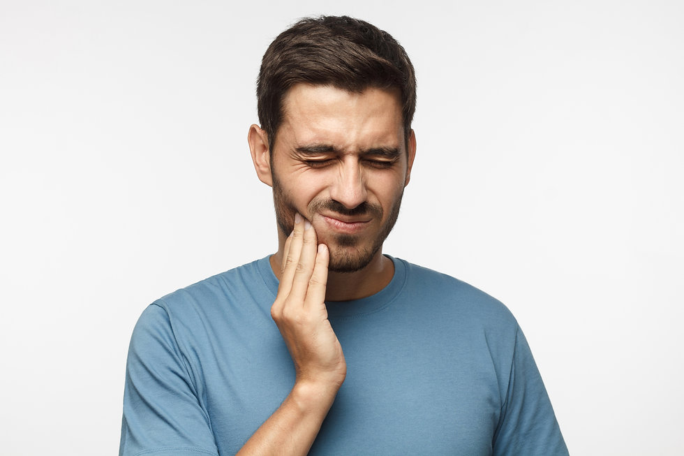 Tooth ache concept. Indoor shot of young male feeling pain, holding his cheek with hand, s