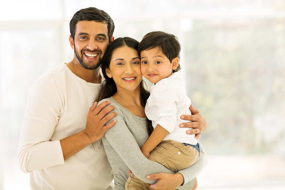 portrait of happy indian family of three standing indoors.jpg