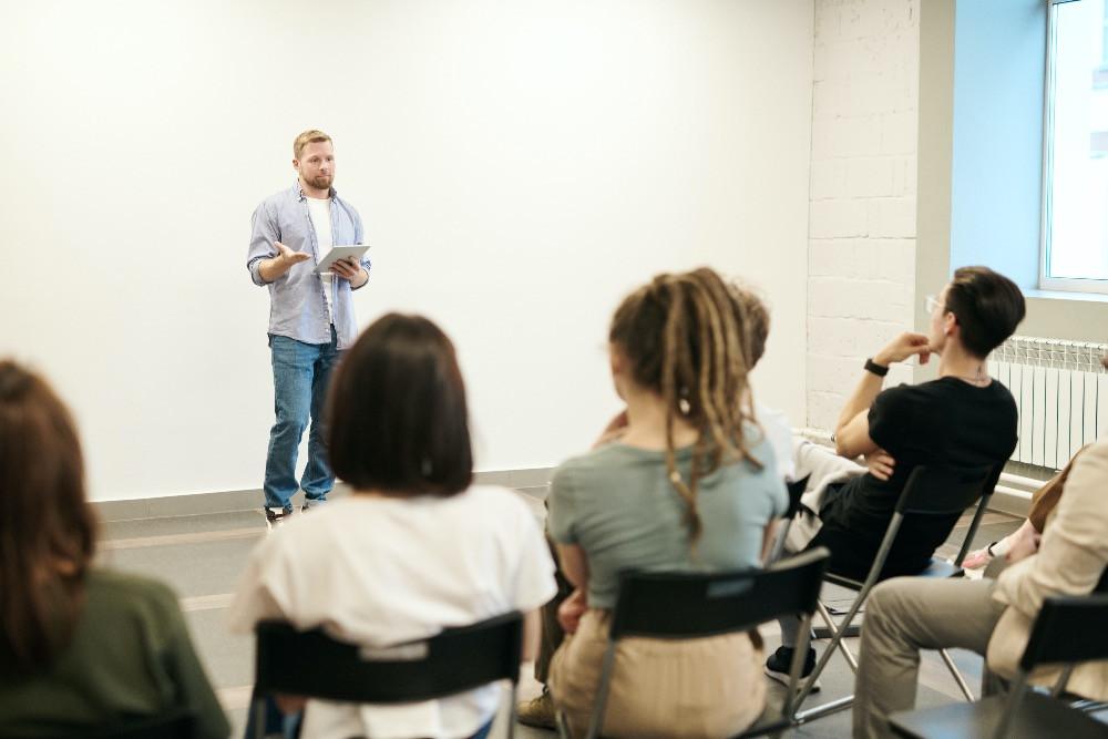 Man presenteert voor aandachtig luisterend publiek.