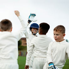 Young happy cricketers cheering on the f
