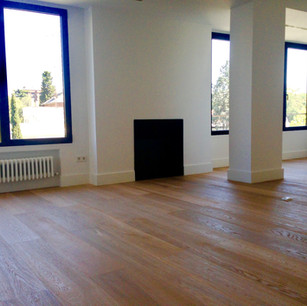 Salón con ventanales a medida y hogar minimalista