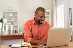 bigstock-Smiling-black-man-using-laptop-306851869