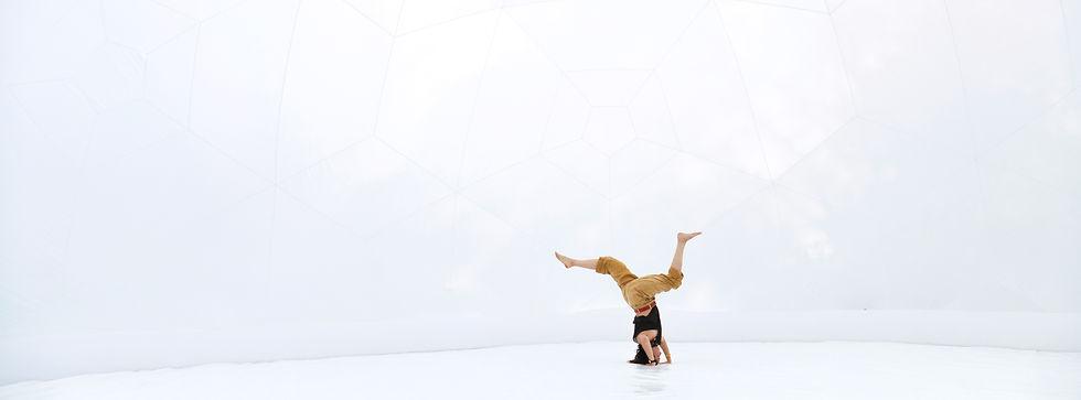 a person cartwheels inside a white dome