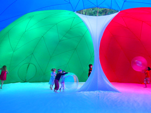 Pneuhaus RGBubble Inflatable Art Architecture Experimental Experience Design Rainbow Light Art Inspired by Nature Physics of Light Tent Event Space Immersive Interactive Installation Art All Ages Family Public Art Festival Silent Disco Color Art Minimal TriColor Red Blue Green Play Ball Kids Art Childrens ExhibitTextile Art Building Fabric Structure