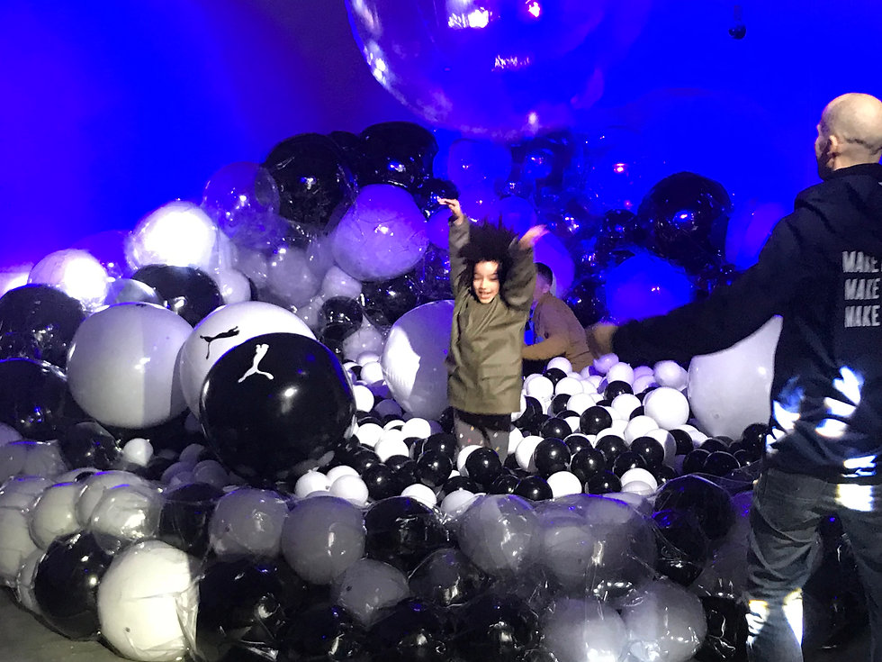 a child jumps out a field of black and white inflatable balls in Pneuhaus's experience design collaboration with PUMA for Art Basel