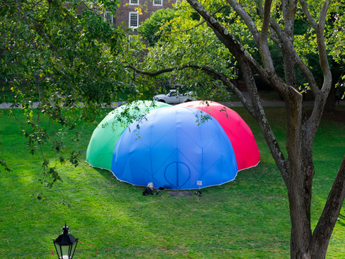 Pneuhaus RGBubble Inflatable Art Architecture Experimental Experience Design Rainbow Light Art Inspired by Nature Physics of Light Tent Event Space Immersive Interactive Installation Art All Ages Family Public Art Festival Silent Disco Color Art Minimal TriColor Red Blue Green Aerial View Textile Art Building Fabric Structure