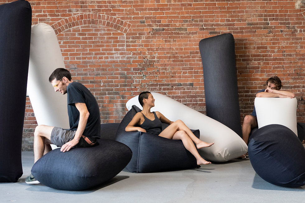 Three people rest in inflatable denim recliners, lounges, and seats made by Pneuhaus for the streetwear brand Khoman.